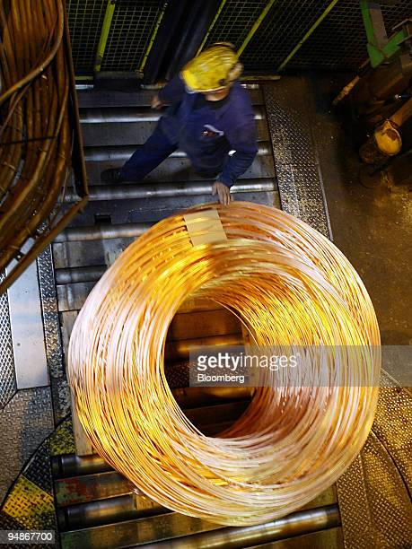 Workers roll copper wire into a coil at the Norddeutsche Affinerie works in Hamburg Germany Thursday October 28 2004 Copper prices rose in London as...