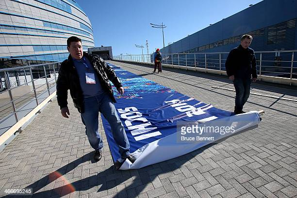 Workers roll out a banner ahead of the Sochi 2014 Winter Olympics at the Olympic Park on February 3 2014 in Sochi Russia