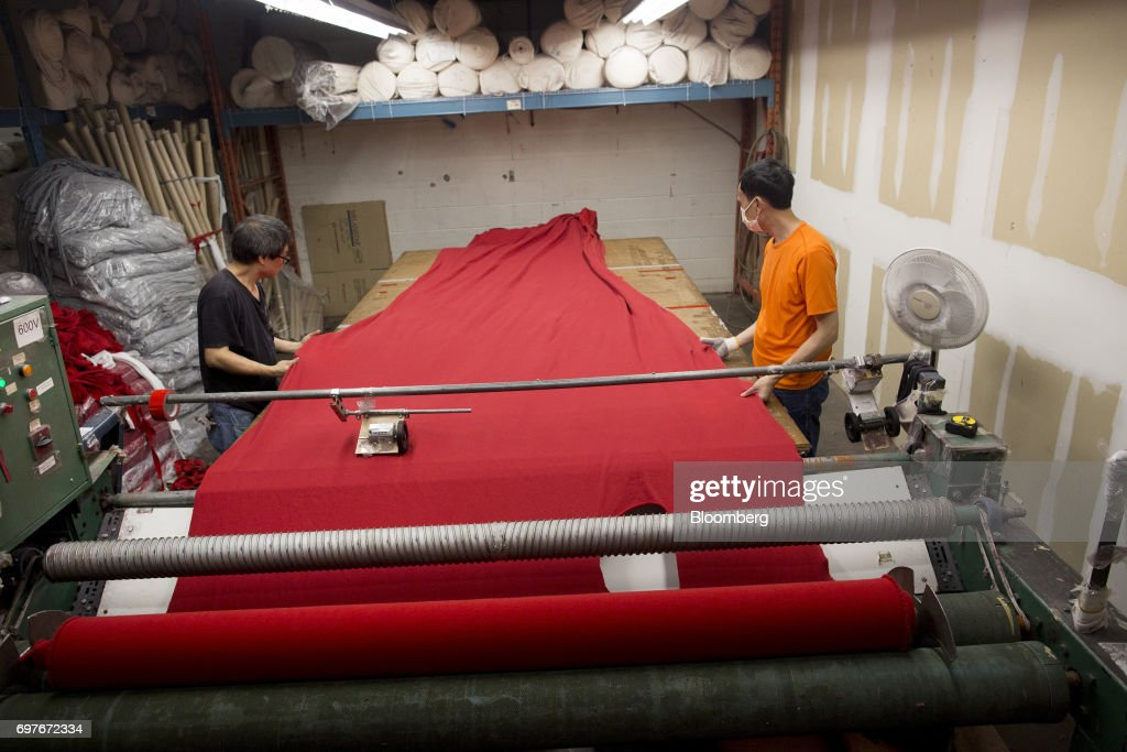 Workers roll out fabric on a table at the WS & Co. production facility in Toronto, Ontario, Canada, on Friday, June 9, 2017. Canada Day celebrates the anniversary of the creation of the Canadian Federation through the North America Act on July 1. Photographer: Brent Lewin/Bloomberg via Getty Images