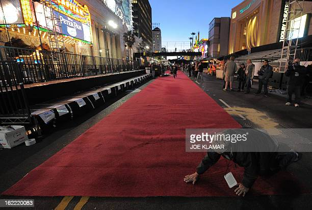 Workers roll out red carpets for the Oscars the 85th Academy Awards outside the Dolby Theatre on Hollywood Boulevard in Hollywood California on...