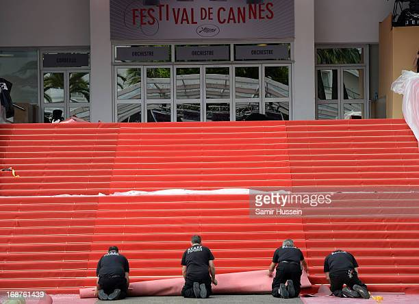 Workers roll out the red carpet before the 66th Annual Cannes Film Festival at Palais des Festivals on May 15 2013 in Cannes France