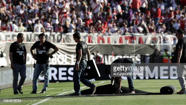 Workers roll up cables and wrap carpets at the Monumental stadium in Buenos Aires on November 24 2018 while authorities decide if the second leg...
