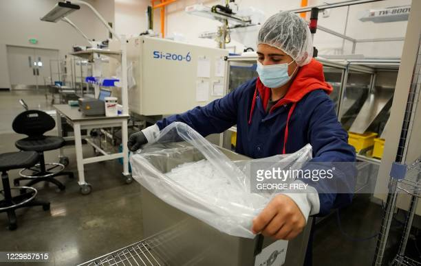 Workers run a plastic injection machine that is producing parts for a saliva based rapid result collection kit to test for COVID19 at Spectrum...