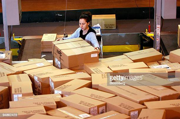 Workers scan and weigh packages at a FedEx Ground facility in Woodbridge, New Jersey on December 16, 2004. FedEx Corp., the No. 2 U.S....