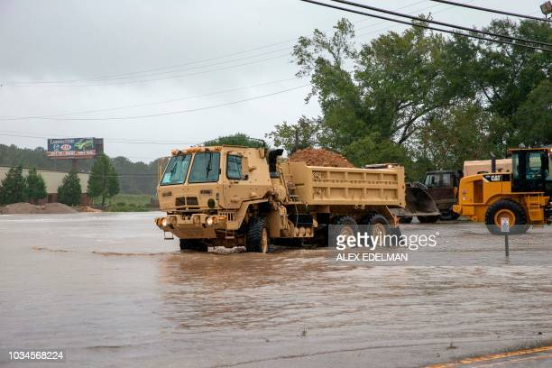 Workers scramble to build a temporary dam to stop rising flood waters from Hurricane Florence in Lumberton North Carolina on September 16 2018...