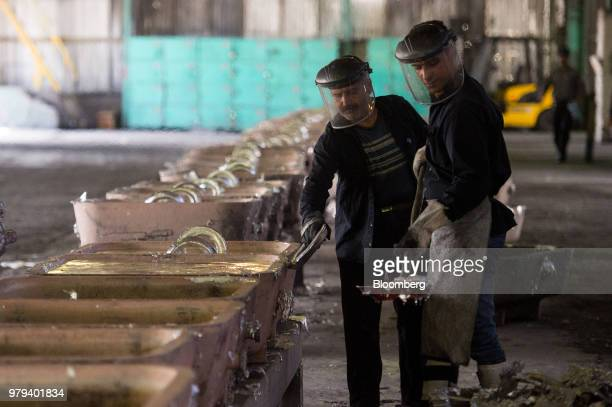 Workers scrape surplus aluminium from ingot molds at the Iran Aluminium Co plant in Arak Iran on Tuesday June 19 2018 As OPEC oil ministers meet in...