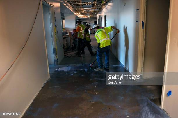 Workers seal the concrete floor in the emergency room area during construction at UCHealth Highands Ranch Hospital scheduled to open early next year...