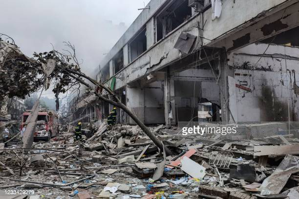 Workers search for victims in a building damaged by a gas line explosion which left at least 12 people dead and nearly 140 others injured in Shiyan,...