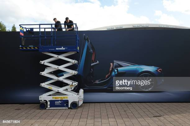 Workers secure a giant advertisement featuring a McLaren 570S Spider luxury automobile manufactured by McLaren Automotive Ltd ahead of the IAA...