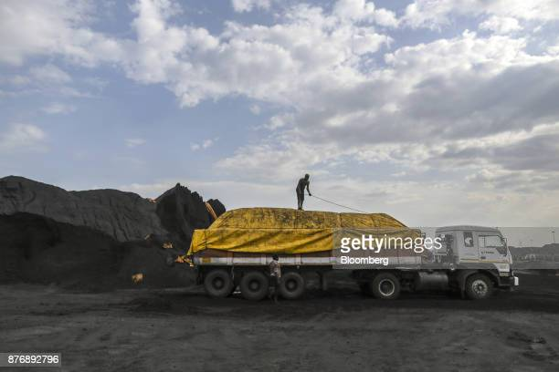 Workers secure a tarp on a truck laden with coal at Krishnapatnam Port in Krishnapatnam Andhra Pradesh India on Monday Aug 11 2017 Growth in gross...