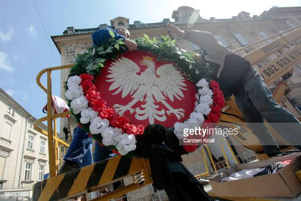 Workers secure the national emblem of Poland with a mourning band over the road are gone where the coffins of the late Polish President Lech...