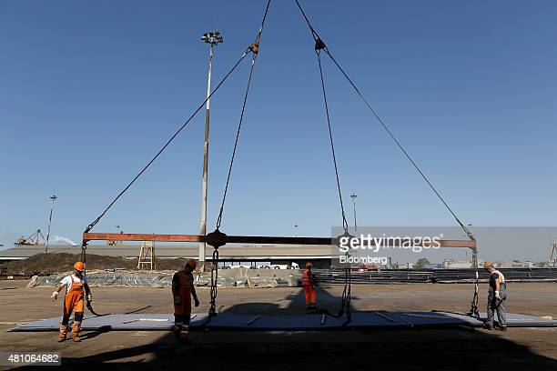 Workers secure winches as they prepare to load sheets of metal onto a cargo ship on the dockside at Thessaloniki port operated by Thessaloniki Port...
