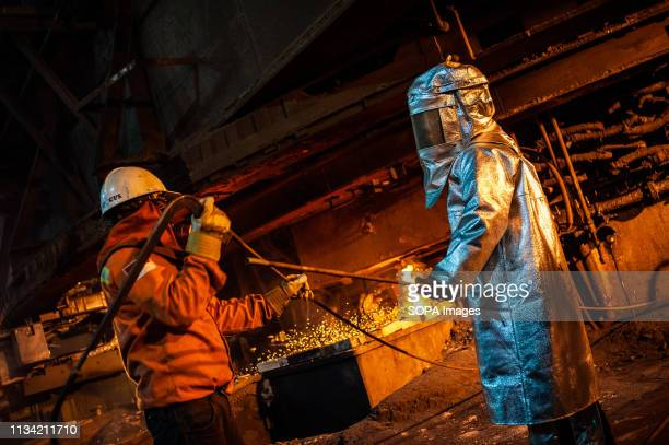 Workers seen supervising the flow of hot liquid metal as it flows from a furnace at the plant. Production of matte nickel at the PT Vale nickel...