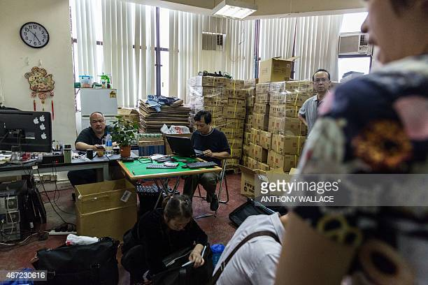 Workers sell goods to customers in their outlet set up for parallel trading within a warehouse in the Sheung Shui district of Hong Kong's New...