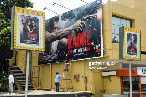 Workers set a banner of the upcoming Bollywood movie 'Radhe,' scheduled to be released on May 13 amidst the Covid-19 coronavirus pandemic, at a...