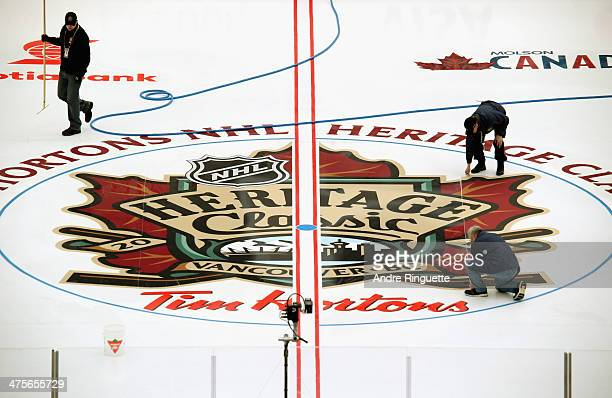 Workers set the center ice logo during the 2014 Tim Horton NHL Heritage Classic build out before the game between the Vancouver Canucks and Ottawa...