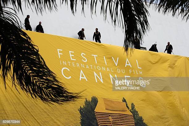 Workers set up a banner of the official poster of the 69th Cannes Film Festival on May 9 2016 on the facade of the Palais des Festivals in Cannes...