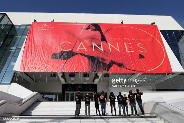 TOPSHOT Workers set up a banner of the official poster of the 70th Cannes Film Festival on May 15 2017 on the facade of the Palais des Festivals in...