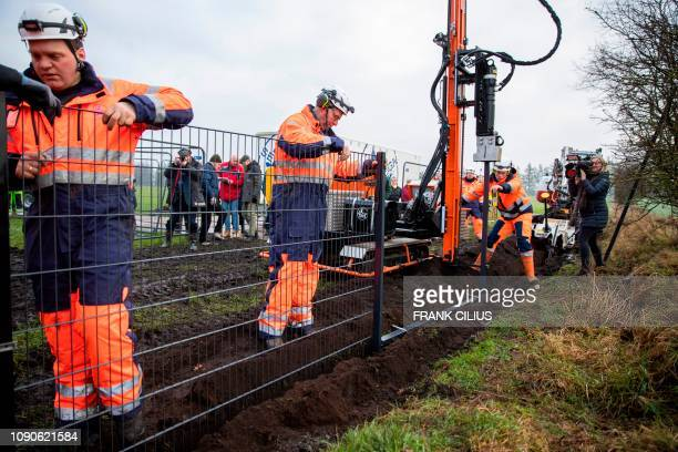 Workers set up a fence at the border between Denmark and Germany on January 28 2019 in Padborg Denmark to prevent wild boars from crossing the border...