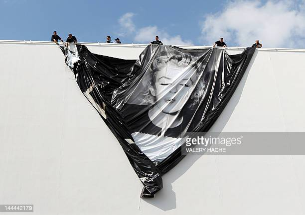 Workers set up a giant official poster of the 65th Cannes' film festival featuring late Marilyn Monroe on May 14 2012 on the facade of the Festivals'...