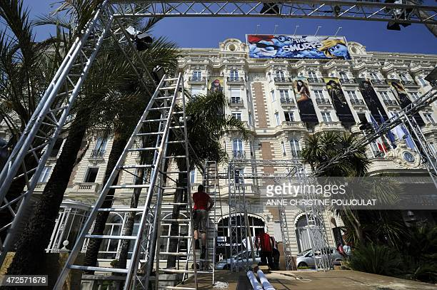 Workers set up a giant poster at the entrance of the Carlton hotel on May 9 2011 on the Croisette in Cannes two days before the opening of the 64th...