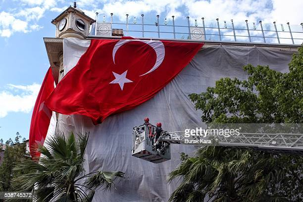 Workers set up a huge Turkish flag on a facade of a building damaged in an explosion in Vezneciler district in downtown Istanbul on June 8 Turkey At...