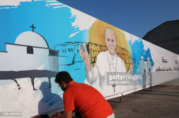 Workers set up a poster of Pope Francis in Arbil, the capital of Iraq's northern autonomous Kurdish region, on March 3 ahead of the first-ever papal...