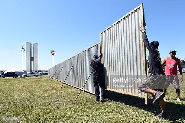 Workers set up a protective fence to separate the demonstrators against the impeachment of President Dilma Rousseff from those supporting it in front...