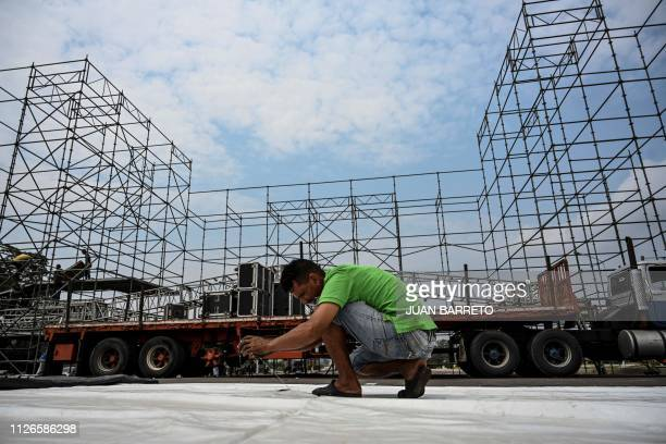 Workers set up a stage for a concert organized by the government of Venzuelan President Nicolas Maduro on Tienditas Bridge in Tachira Venezuela in...