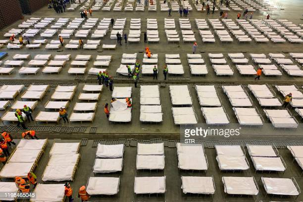 Workers set up beds at an exhibition centre that was converted into a hospital in Wuhan in China's central Hubei province on February 4 2020 The...