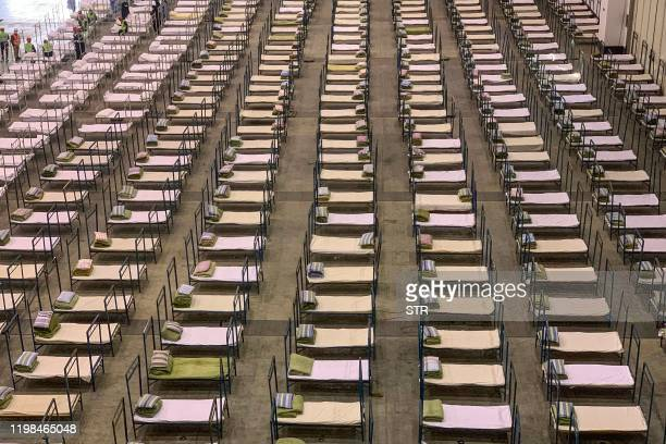 Workers set up beds at an exhibition centre that was converted into a hospital in Wuhan in China's central Hubei province on February 4, 2020. - The...