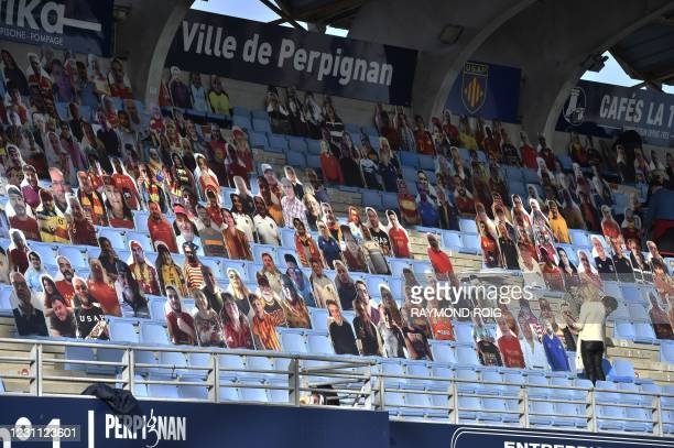 Workers set up cardboard cutouts of rugby supporters in grandstand of the Aime Giral stadium ahead of the French Pro D2 rugby match between Perpignan...