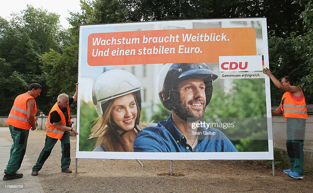 Workers set up election campaign posters of the German Christian Democrats (CDU) on August 6, 2013 in Berlin, Germany. Germany is scheduled to hold federal elections on September 22 and so far current Chancellor Angela Merkel and her party, the German Christian Democrats (CDU), have a strong lead over the opposition.