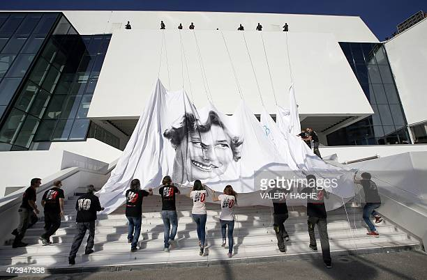 Workers set up the official poster of the 68th Cannes' film festival on May 11 2015 on the Festivals' palace facade in Cannes southeastern France AFP...
