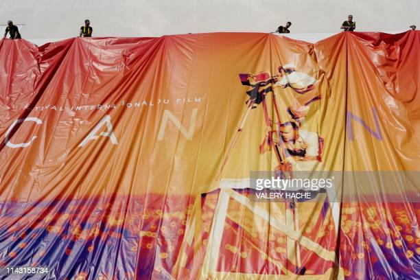 Workers set up the official poster of the 72nd Cannes Film Festival on the facade of the Palais des Festivals in Cannes southeastern France on May 12...