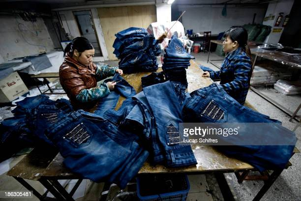 Workers sew blue jeans in a little workshop by the street on February 10 2012 in Xintang Guangdong province ChinaThe town of Xintang nicknamed the...