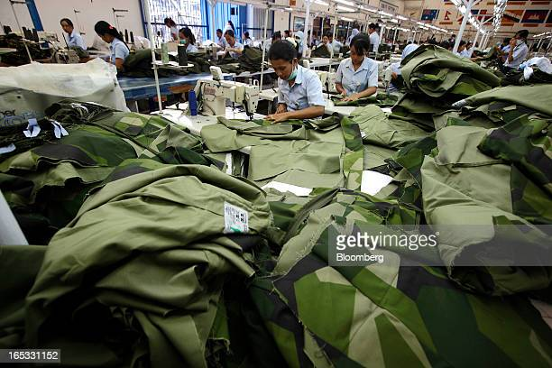 Workers sew military combat uniforms on the production line in the garment area at a PT Sri Rejeki Isman factory in Sukoharjo Java Indonesia on...