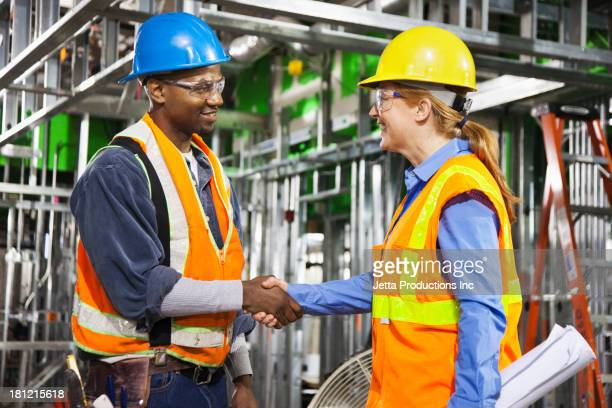Workers shaking hands on site
