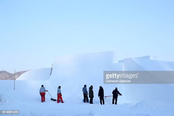 Workers shape a kicker at the Olympic slopestyle course at Phoenix Snow Park on February 4 2018 in Pyeongchanggun South Korea