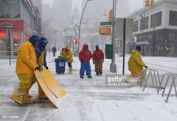 Workers shovel a sidewalk of snow and ice on January 4 2018 in Brooklyn New York The US National Weather Service warned that a major winter storm...