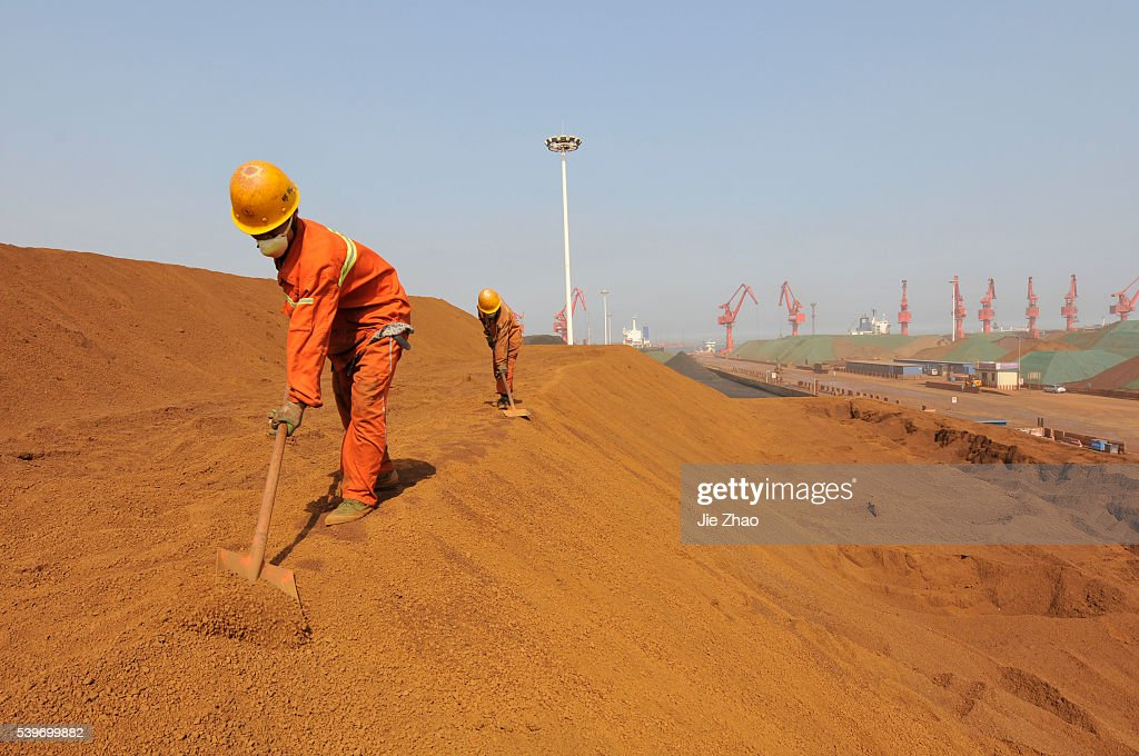 Workers shovel iron ore from Australia while it is being offloaded at Rizhao Port : News Photo