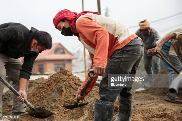 Workers shovel sand at a construction site for a road operated by Shanghai Construction Group Co in the Kalanki Chowk area of Kathmandu Nepal on...