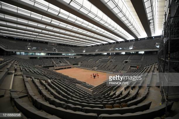 Workers show the newly built roof of the Philippe Chatrier central tennis court at the Roland Garros stadium on May 27 in Paris The Roland Garros...