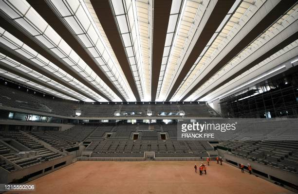 TOPSHOT Workers show the newly built roof of the Philippe Chatrier central tennis court at the Roland Garros stadium on May 27 in Paris The Roland...