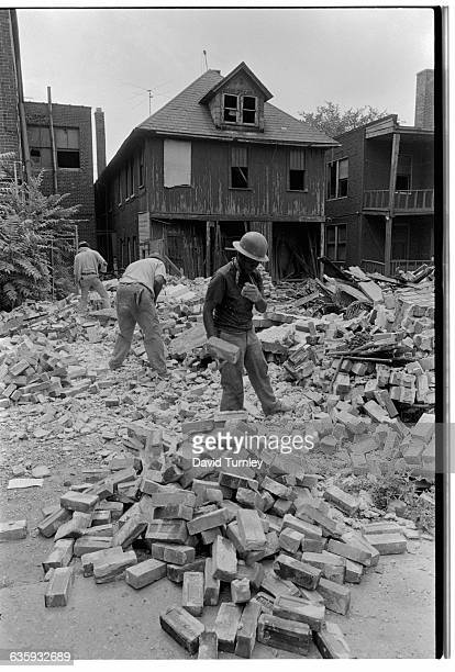 Workers sift through the rubble of a demolished home
