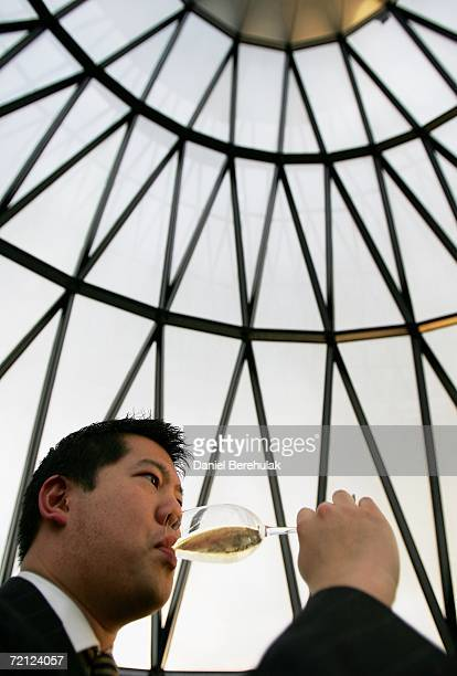 A workers sips champagne from a glass on the top floor of St Mary's Axe nicknamed The Gherkin on June 2 2006 in London England The famous London...