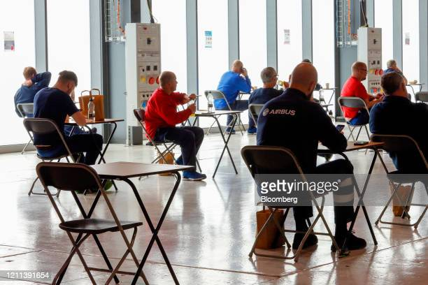 Workers sit at individual tables as they practice social distancing measures during a break at the Airbus SE assembly plant in Broughton UK on...