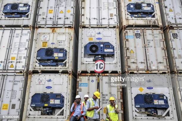 Workers sit in front of containers stacked in a yard at Krishnapatnam Port in Krishnapatnam Andhra Pradesh India on Monday Aug 11 2017 Growth in...