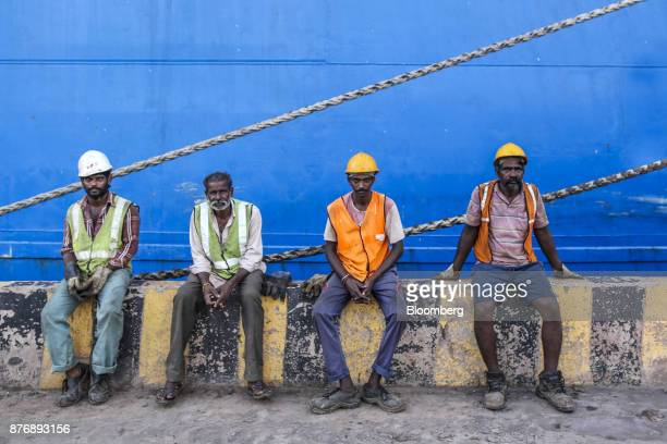Workers sit in front of the Da Dan Xia cargo ship not pictured at Krishnapatnam Port in Krishnapatnam Andhra Pradesh India on Friday Aug 11 2017...