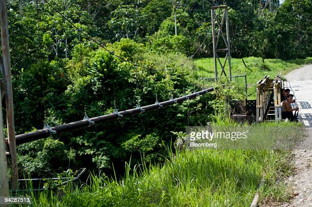 Workers sit near an oil pipeline that runs through the Ecuadorian Amazon rainforest near Yasuni National Park in Orellana Province Ecuador on Tuesday...